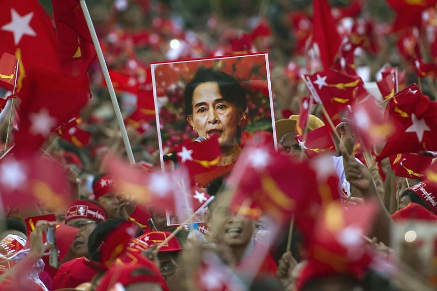 Supporters of Myanmar opposition leader Aung San Suu Kyi hold posters bearing her image as she speaks during a campaign rally on Nov 1, 2015.