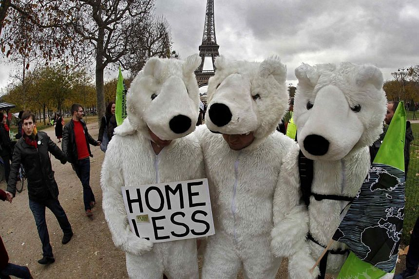 Three environmentalists wear polar bear costumes in a demonstration in Paris, France, during the World Climate Change Conference on Dec 12, 2015.