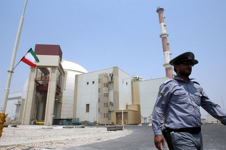 A file photograph showing an Iranian security officer walking in front of the nuclear power plant in Bushehr, southern Iran, on Aug 21, 2010.