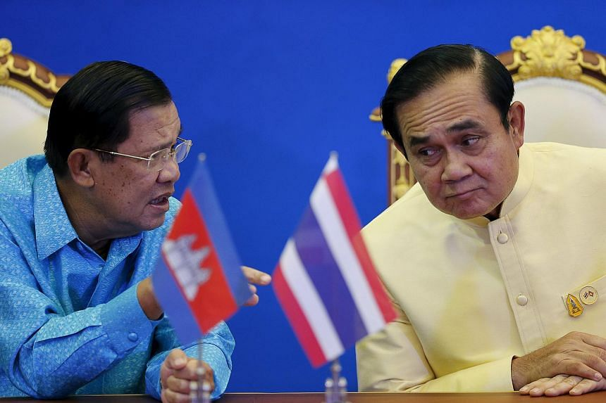 Cambodia's Prime Minister Hun Sen (left) talks to Thailand's Prime Minister Prayuth Chan-ocha during an agreement signing ceremony at the Government House in Bangkok.