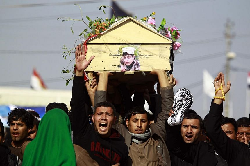 Iraqi mourners carry the body of one of the soldiers who were killed the previous day in a so-called friendly fire from a US-led coalition aircraft west of Baghdad.