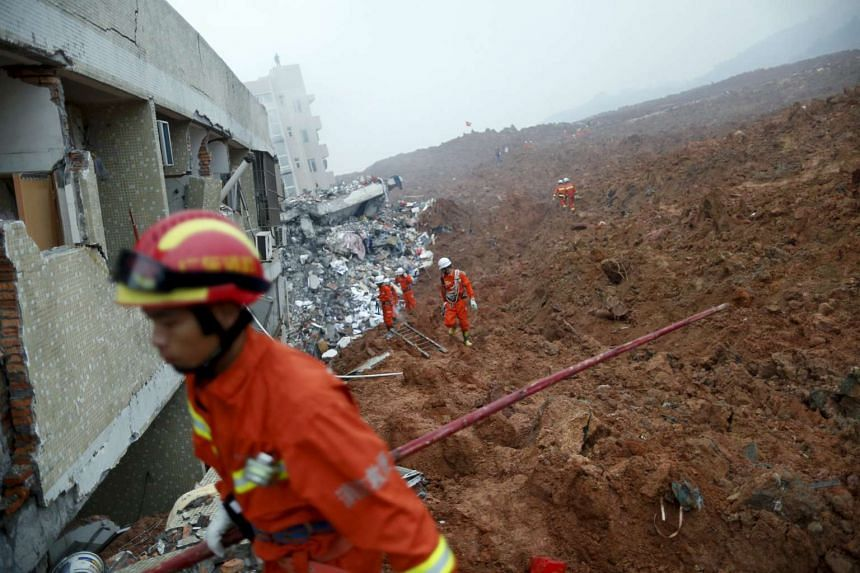 Firefighters searching for survivors near a damaged building at the site of a landslide in Shenzhen, Guangzhou on Dec 20, 2015.