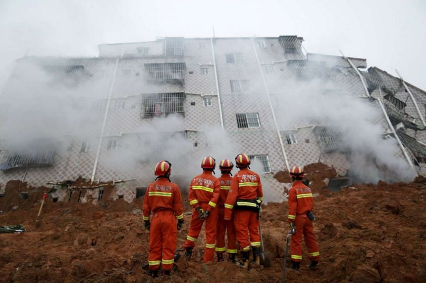 Firefighters looking on as smoke rises from a damaged building in the aftermath of a landslide on Dec 20, 2015.