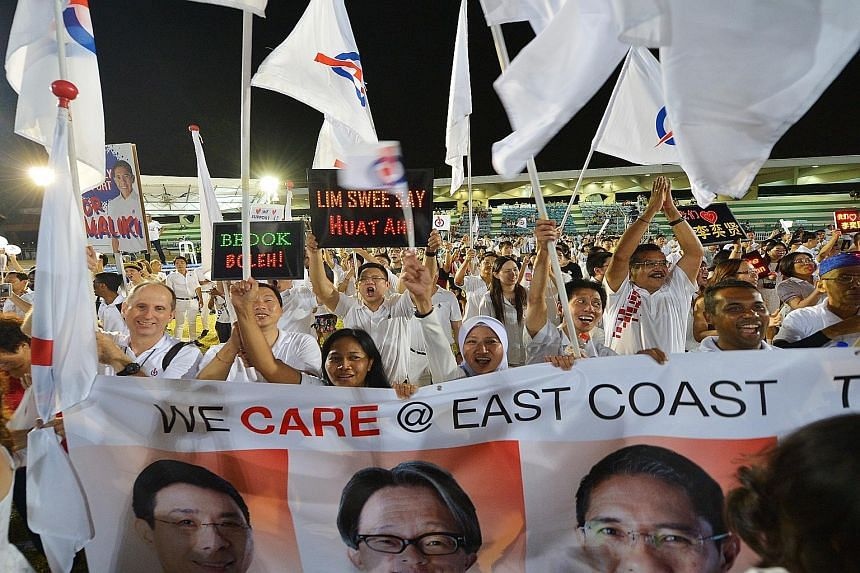 Jubilant PAP supporters with a poster of the East Coast GRC team, comprising Mr Lim Swee Say, Mr Lee Yi Shyan, Dr Mohamad Maliki Osman and Ms Jessica Tan, at Bedok Stadium in September. The GRC was one that some analysts had believed could be the nex