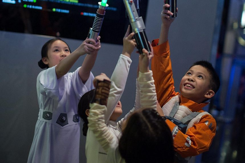 Children dressed in Star Wars costumes playing with toy lightsabers at a cinema in Hong Kong last Thursday, as the latest film in the Star Wars franchise opened in cinemas across the world.