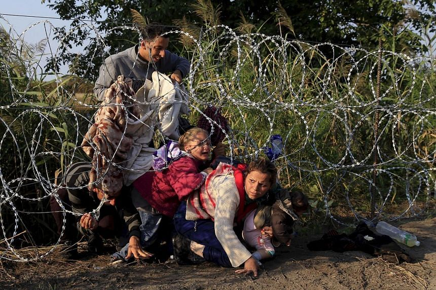 Syrian migrants crossing under a fence as they enter Hungary at the border with Serbia, near Roszke, in August. By the time this year ends, Europe would have received at least 1.2 million refugees. This is the biggest mass movement in a generation.