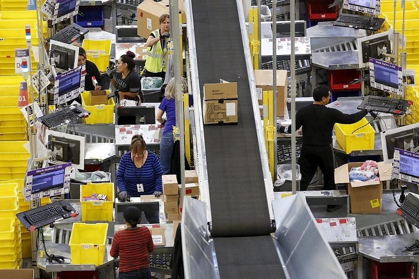 Workers prepare orders for customers at the Amazon Fulfilment Centre in Tracy, California. Despite a slow pace of economic recovery, the US labour market is showing all of the tightening that is typical of any previous rapid recovery.