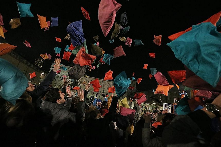 """Laughter filled the night as people threw pillows into the air, as part of """"Pillow Fight"""", an event organised by Italian theatre company Il Melarancio in Piazza Castello in Turin on Friday. More than 700 colourful pillows were brought to the piazza f"""