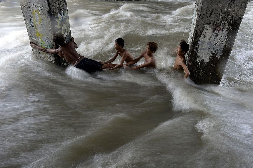 Children swimming in a creek swollen with floodwaters in Manila yesterday. The storm, known locally as Onyok, weakened into a low pressure area after hitting land late on Friday, but continued to bring more rain to Mindanao and the central Visayas is
