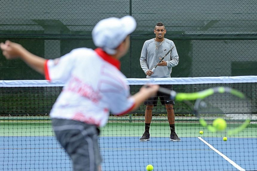 Australia's Nick Kyrgios , (facing camera), who plays for the Singapore Slammers, conducting a clinic for juniors at the Marina Square rooftop court yesterday.