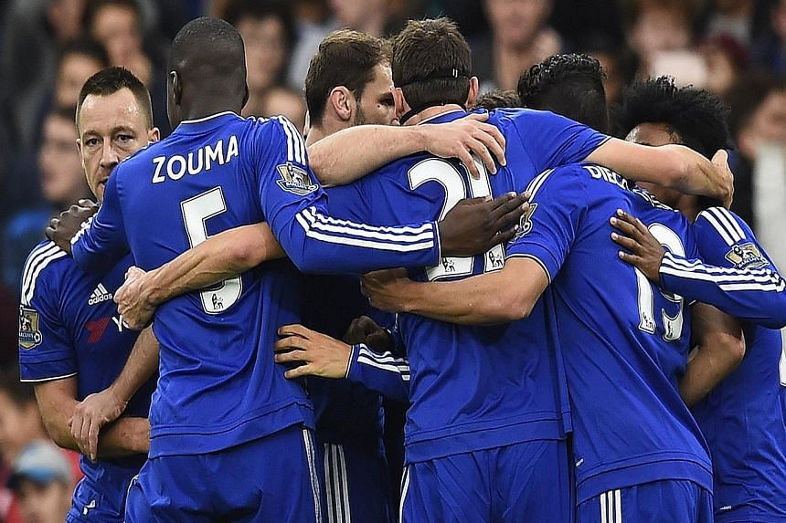 Pedro (hidden) celebrates with team-mates after scoring the second goal for Chelsea at Stamford Bridge.