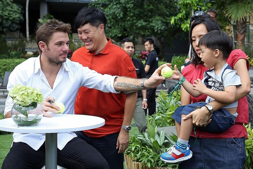 Tennis world No. 4 Stan Wawrinka handing three-year-old Caleb Lau an autographed ball at OUE Twin Peaks yesterday morning. The Swiss two-time Grand Slam champion, who is in town as the marquee player for the OUE Singapore Slammers, spent time meeting