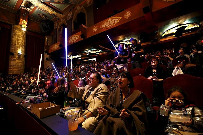 Moviegoers, eager to see the first Star Wars movie in a decade, cheering and waving light sabers before the first screening of The Force Awakens at the TCL Chinese Theatre in Hollywood, California, on Thursday.