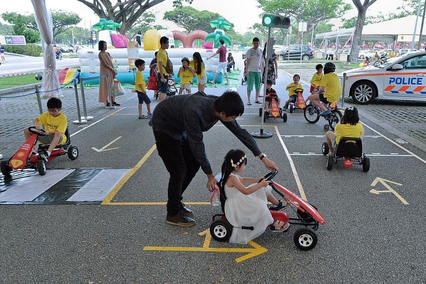 Children learning basic traffic rules at a road-safety circuit at the AAS carnival held at Carpark 5 at Kallang Leisure Park yesterday.