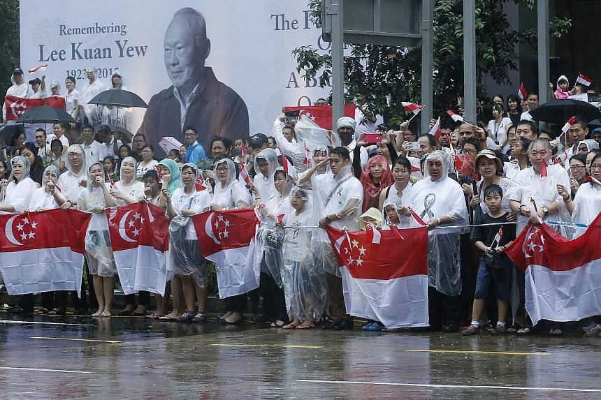 Two events that stand out this year are the death of founding prime minister Lee Kuan Yew and Singapore's golden jubilee as an independent nation. Above, left: Mourners braving the rain outside the NTUC headquarters at 1 Marina Boulevard as they wait