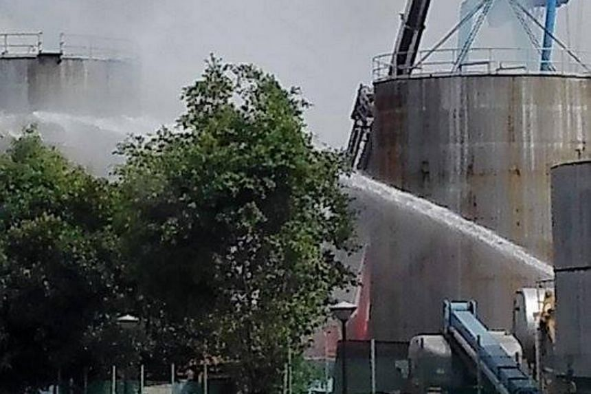 SCDF officers spraying water at a fire which broke out at an unused storage tank at Sime Darby Edible Products around 3pm on Dec 20, 2015.