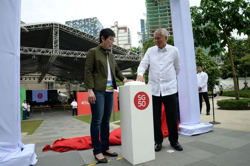 Singapore Ambassador Kok Li Peng (left) and Philippine Foreign Minister Albert del Rosario opening the #SG50inManila fair on Dec 20, 2015.