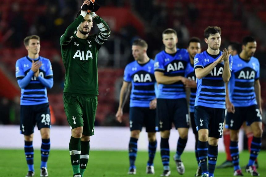 Tottenham Hotspur's French goalkeeper Hugo Lloris (second left) celebrates on the pitch with his team.