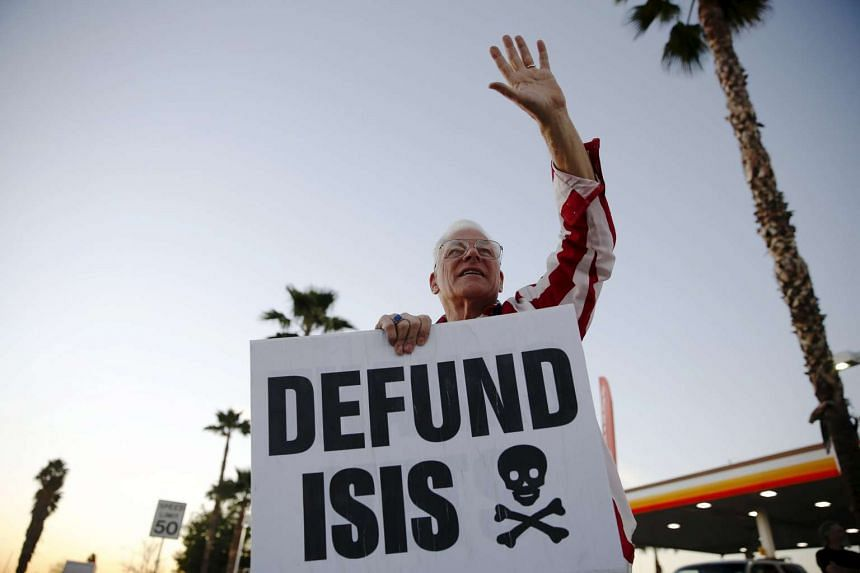 Robert Newman protests against ISIS across from a makeshift memorial for victims of the San Bernardino shooting.