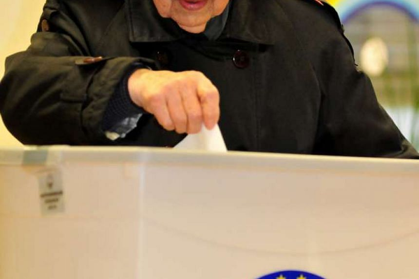 A woman casts her ballot at a polling station in Ljubljana, Slovenia on Dec 20, 2015, during the referendum to repeal the law allowing same-sex marriages.