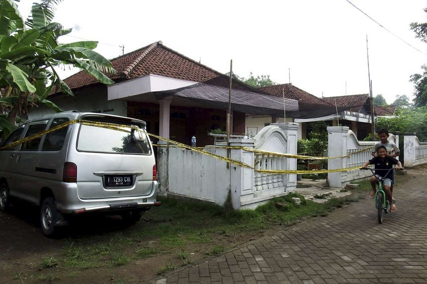 Children ride a bike past a house with police tape around it, following a raid by anti-terror police in Mojokerto, East Java, on Dec 20, 2015.