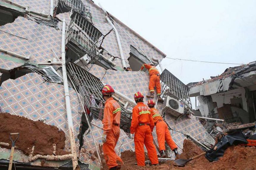 Rescuers sifting through rubble looking for survivors after a landslide left everything covered in mud.