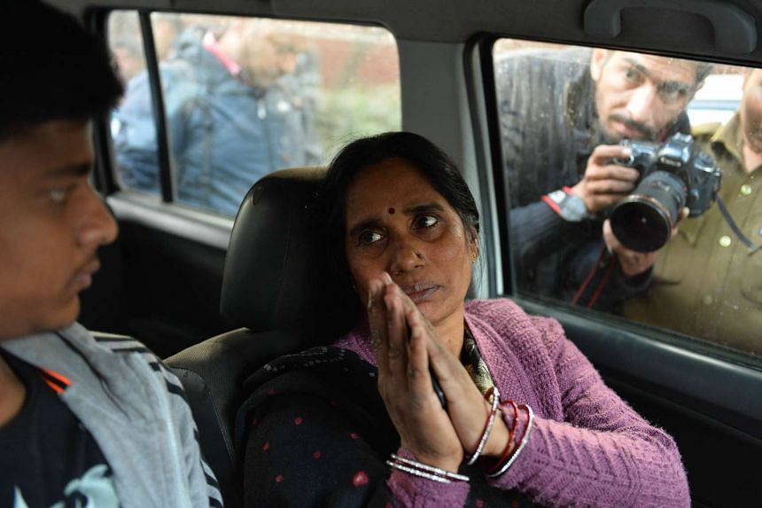 The mother of Indian gangrape victim 'Nirbhaya' gestures as she sits in a vehicle as she heads to a rally in New Delhi on Dec 20, 2015, held to protest the release of a juvenile rapist.