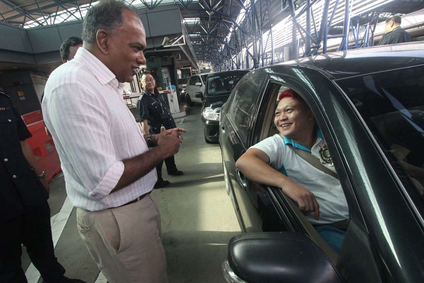 A driver sharing with Minister for Home Affairs and Law K Shanmugam (left) his travel journey concerns at the Woodlands Checkpoint on Dec 19, 2015.