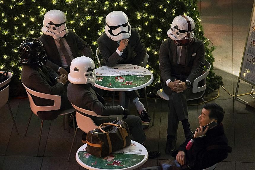 Fans wearing Stormtrooper helmets in a food court ahead of the first public screening of The Force Awakens in Roppongi Hills in Tokyo. Fans posing with members of Malaysia's Star Wars Fan Club dressed as various characters before watching The Force A