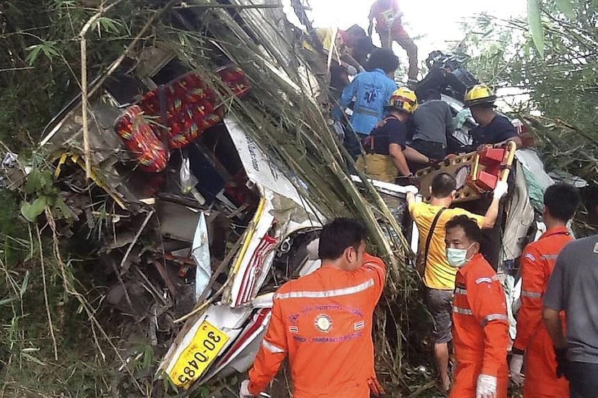 Rescue workers at the wreckage of the bus after it plunged off a road in Doi Saket district, Chiang Mai, yesterday. The bus, carrying 23 people, hit a car and ran off a curve in the road. Ten other people in the bus were injured and are being treated