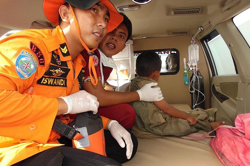 Two members of a search-and- rescue team with a young survivor in Siwa. The vessel was ferrying 118 people around Sulawesi island when it sent out a distress signal last Saturday afternoon.