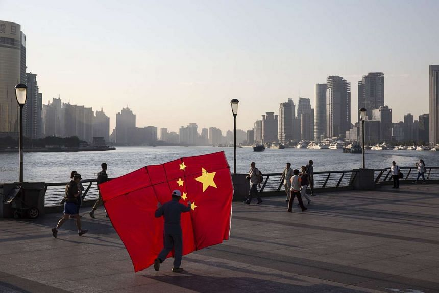 A man carrying a kite in the shape of the Chinese national flag walking along the Bund in Shanghai.