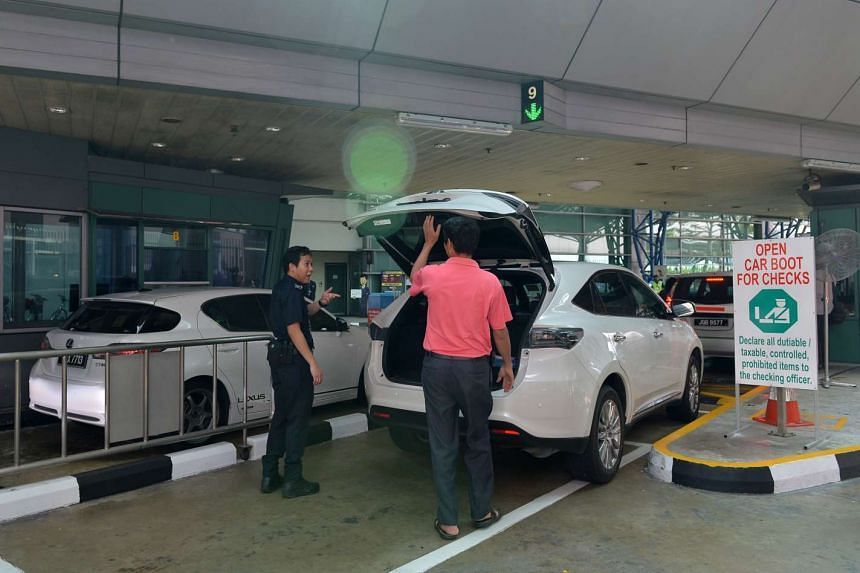 A Customs officer inspecting the boot of a car moving through Woodlands Checkpoint on Dec 21, 2015.