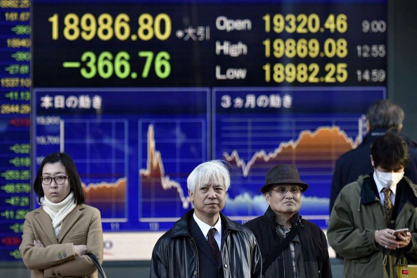 Pedestrians stand before a stock market indicator board in Tokyo, Japan, Dec 18, 2015.