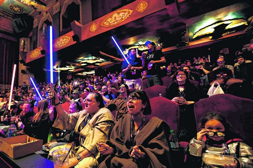 Moviegoers cheer and wave lightsabers before the first showing of Star Wars: The Force Awakens at the TCL Chinese Theatre in Hollywood on Thursday last week.