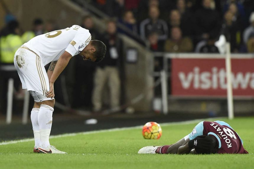 Swansea's Kyle Naughton looks on as West Ham's Cheikou Kouyate lies injured in Sunday's scoreless draw.