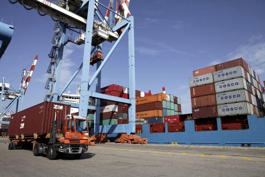 A truck removes a shipping container during the unloading of a cargo vessel at the Port of Haifa in Haifa, Israel.