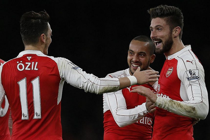 Arsenal's French striker Olivier Giroud celebrates scoring his team's second goal with Arsenal's English midfielder Theo Walcott and Arsenal's German midfielder Mesut Ozil during the English Premier League match at the Emirates Stadium in London on D