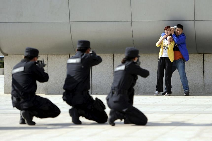 Chinese police officers take aim with their weapons at a man playing the role of an attacker during an anti-terrorism drill in this May 7, 2014, file picture.