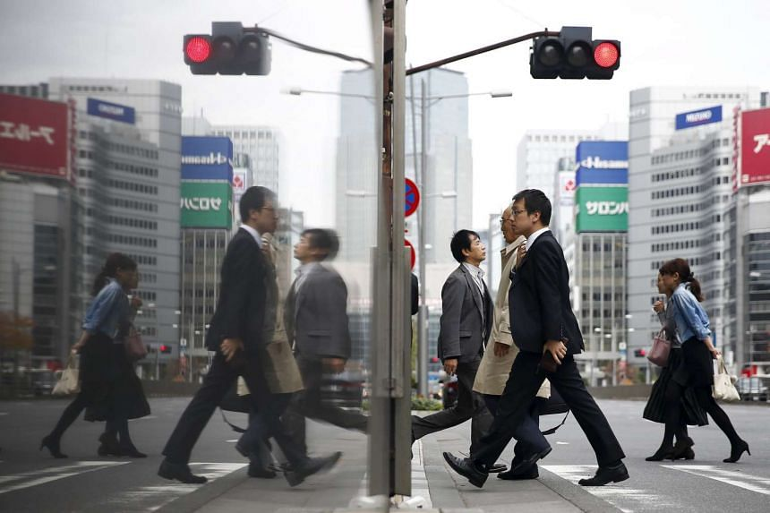 People cross a street in a business district in central Tokyo, Japan, Dec 8, 2015.