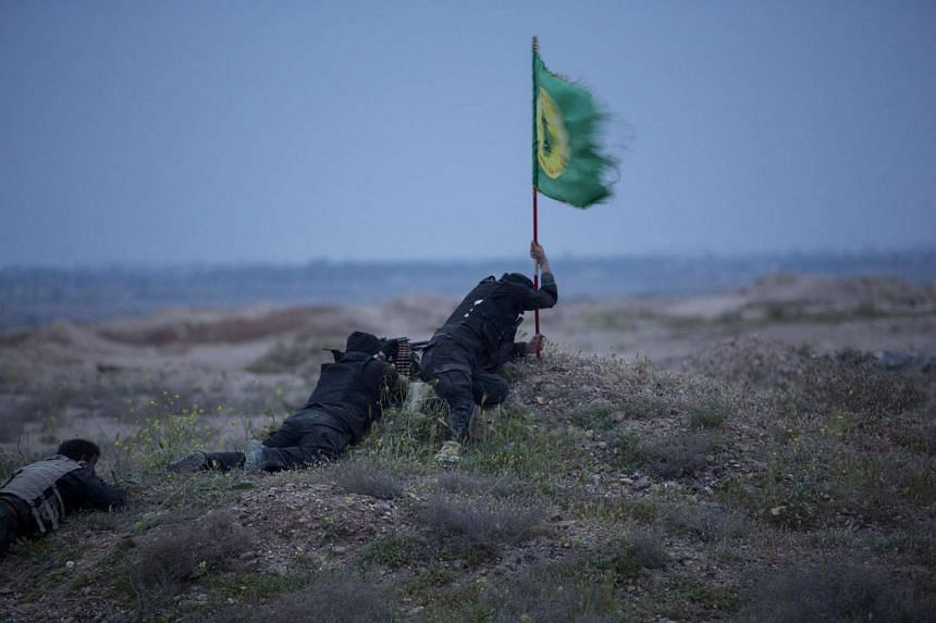 Shi'ite fighters, known as Hashid Shaabi, clash with Islamic State militants as one tries to put a Shi'ite flag in the ground, in northern Tikrit, Iraq, in this March 12, 2015 file photo.