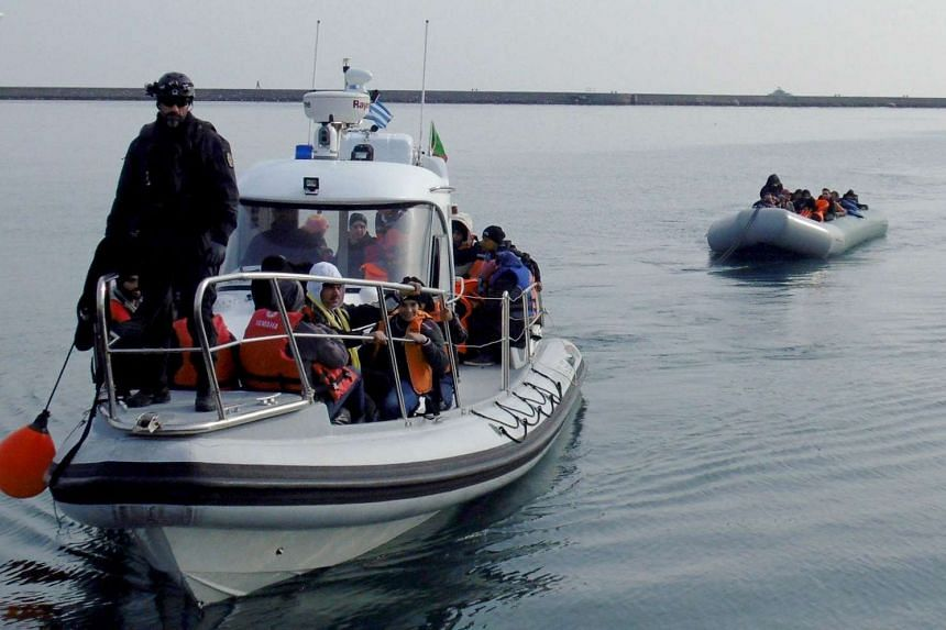 A group of refugees and migrants are towed in a dinghy by a coast guard patrol boat near the Greek island of Lesbos.
