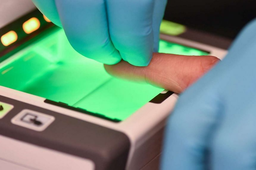 An employee of the German Federal Office for Migration and Refugees (Bamf) makes an electronic finger print scan of a refugee at a branch office of the Bamf in Heidelberg, Germany, on Dec 18, 2015.