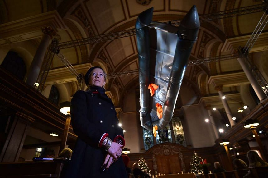 "British artist Arabella Dorman poses with her art installation entitled ""Flight""- a capsized boat, complete with life jackets, used by refugees to get to the Greek island of Lesbos- suspended in the nave of St. James's Church in London, on Dec 21, 20"