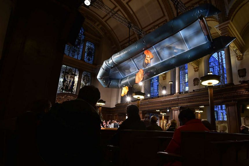 """Flight"", an art installation by British artist Arabella Dorman, shows a capsized boat, complete with life jackets, used by refugees to get to the Greek island of Lesbos, suspended in the nave of St. James's Church in London, on Dec 21, 2015."
