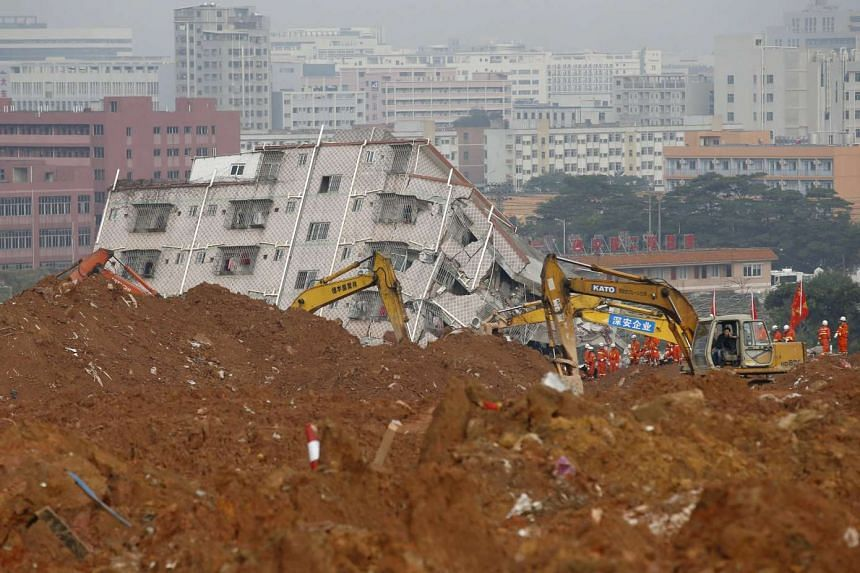 Rescue workers work around a damaged building in the industrial park hit by a landslide in Shenzhen, Guangdong province, Dec 22, 2015.