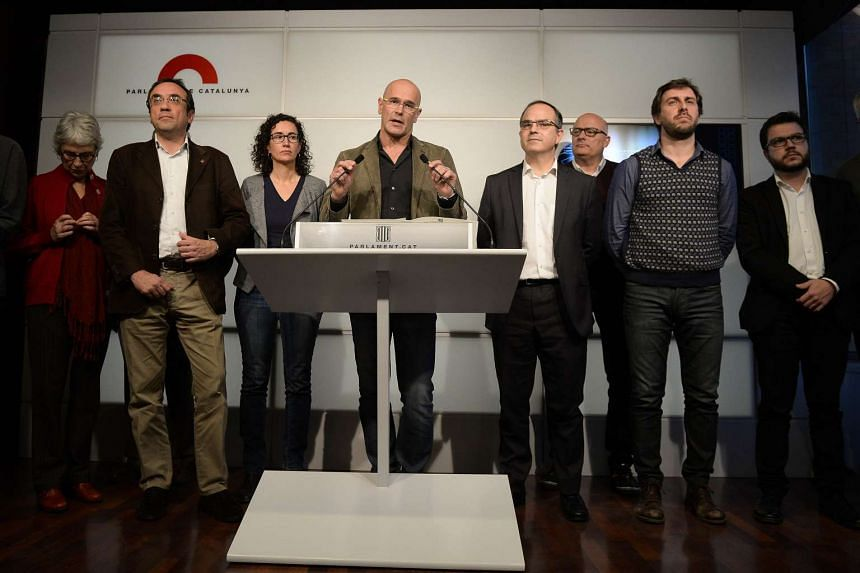 Leader of the Catalan pro independence coalition Raul Romeva (centre) speaks, flanked by other coalition members.
