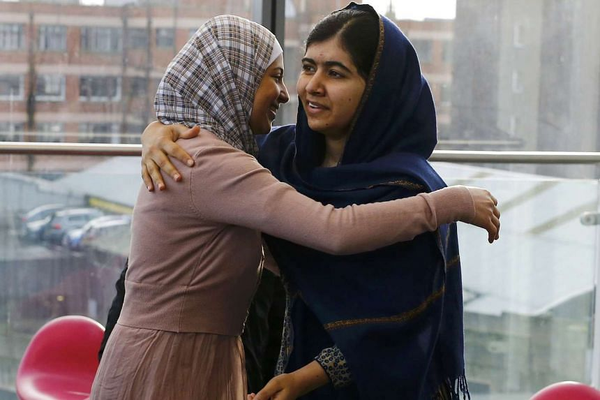 Malala Yousafzai (right) greets Muzoon Almellehan in Britain.