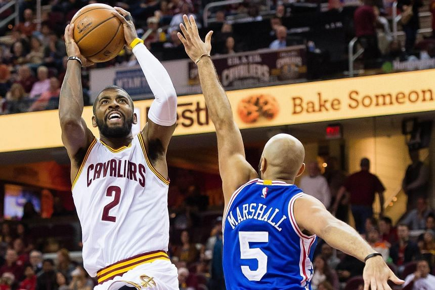Kyrie Irving (left) of the Cleveland Cavaliers shooting over Kendall Marshall of the Philadelphia 76ers during the second half at Quicken Loans Arena on Sunday. The Cavaliers defeated the 76ers 108-86.