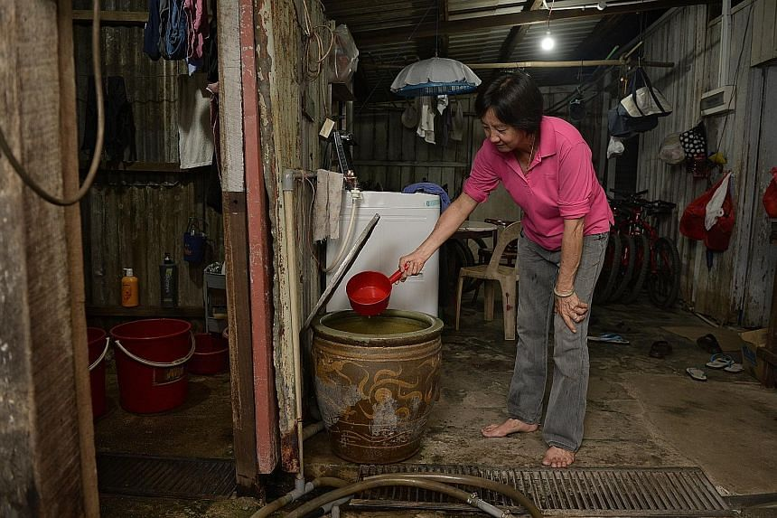 Pulau Ubin resident and bicycle rental shop owner Yang Hui Qing, 60, scooping water, which came from a well, for cooking yesterday. She boils the water first before using it.